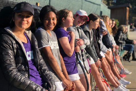 Members of the middle school tennis team lean against the wall waiting to play their next match. Both playing groups, green team and purple team, made it to playoffs for the first time in Archer history.