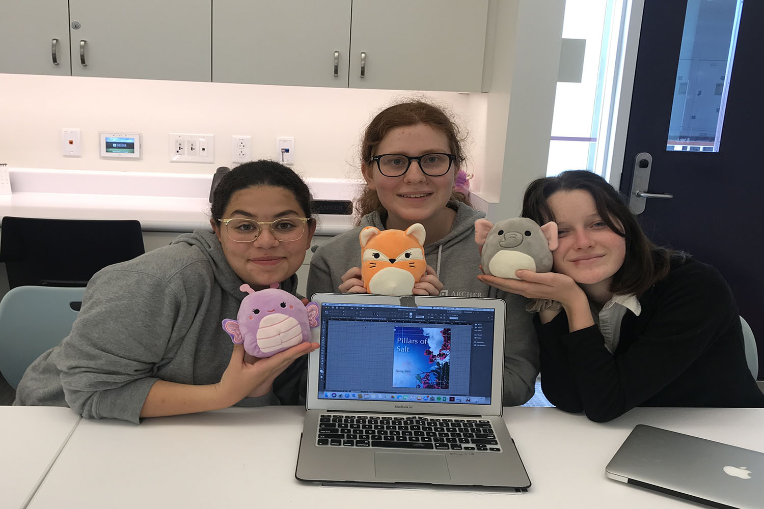 Juliet Youssef '19, Josie Gordon '20 and Madis Kennedy '21 pose with some of the many stuffed animals in the creative writing class. The class biannually contributes to and curates a literary magazine, Pillars of Salt.