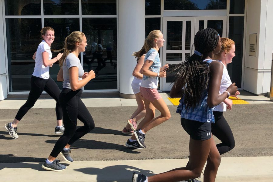 The varsity cross country team, including senior Sophie Larbalestier, runs during an on campus practice. Larbalestier has been running cross country since the tenth grade and is team captain this year.