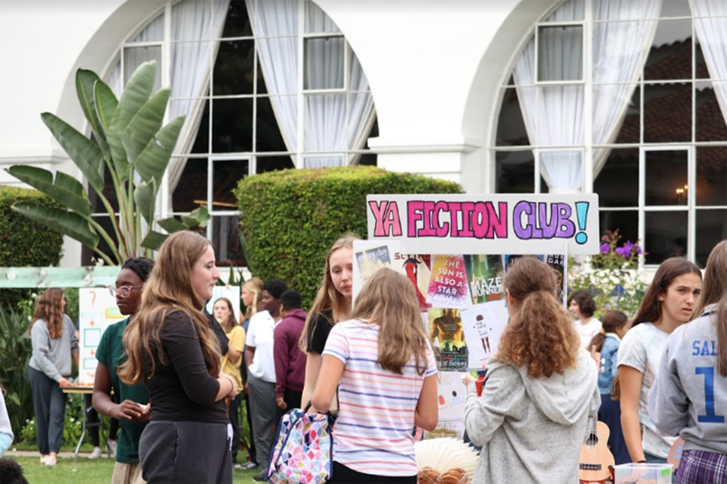 Students gather around the YA Fiction Club booth at the annual club fair. The club fair is held annually in the courtyard in September and spans one lunch period.