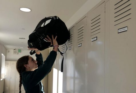 Sophomore varsity tennis player Naya Ben-Meir puts her tennis bag above the lockers at the start of school day. Ben-Meir has been on the varsity tennis team since her freshman year.