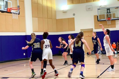 Junior Ariel Heimanson attempts a shot in the first varsity basketball game of the season against Vistamar School on Nov. 19. The team won with the score of 30-21.