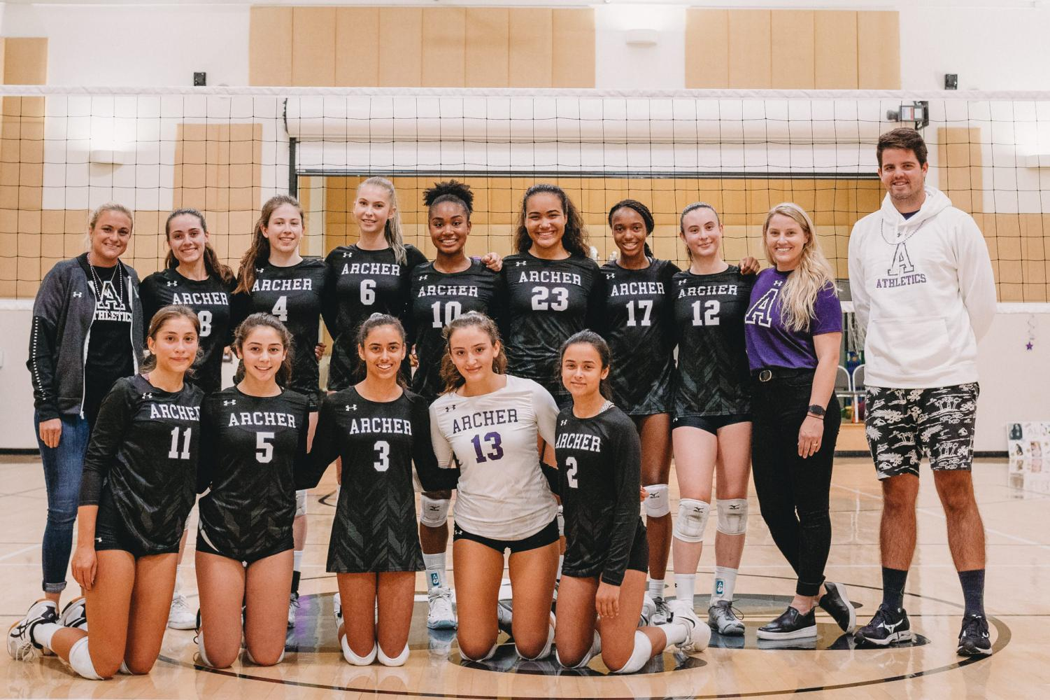 The+varsity+volleyball+team+poses+for+a+group+shot+after+a+victory+against+the+Buckley+school+on+senior+night.+The+team+won+3-0.+