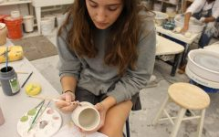 Junior Bella Morgan, founder of of Organic Matter Pottery, works in the Archer ceramics studio painting a mug.