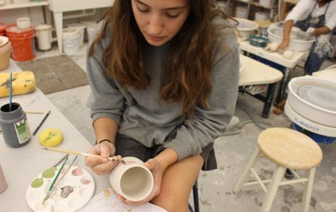 Junior Bella Morgan, founder of of Organic Matter Pottery, works in the Archer ceramics studio painting a mug.
