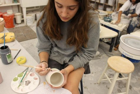 "Junior Bella Morgan, founder of of Organic Matter Pottery, works in the Archer ceramics studio painting a mug. ""[Ceramics is] a strong passion of mine and I dedicate a lot of my time to it because it something very relaxing and stress free,"" Morgan said."