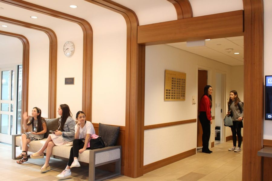 Three applicants sit in a couch in the admissions area, waiting to be called in for an interview. They were also given magazines from Archer to browse through as they wait.
