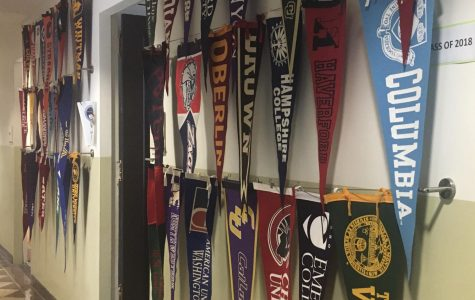 Various college pennants hang in the admissions hallway. Juniors continue the college process until May 1 of their senior year, National College Decision Day, when they hang a pennant from the college they have chosen to attend.