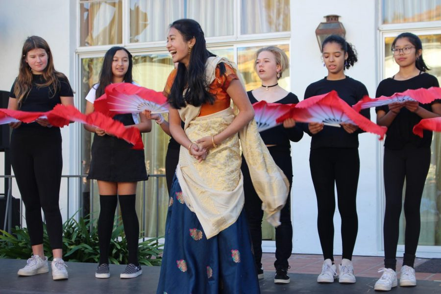 While modeling traditional dress during the fashion show, Kaitlyn Kim ('21) laughs on stage as dancers use fans to decorate the stage with color. The fashion show participants modeled different clothing items from countries within Asia.