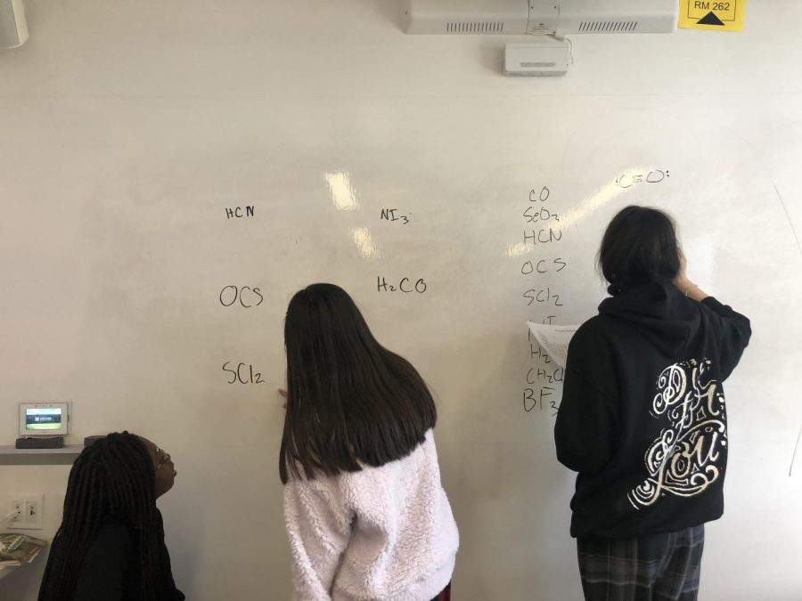 Tenth grade students Chidimma Nwafor, Alexa Marsh and Andrea Ramirez study for a chemistry final. They are helping each other through practice problems from their chemistry packets.