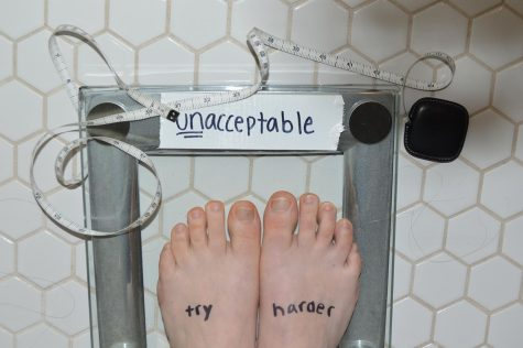 "In this photo staged by junior Emily Eshel, a girl stands on a scale that reads ""unacceptable"" where the weight is supposed to be located. Eshel created this image for an English project exploring beauty ideals. Sophomore Leah Abazari said that the pressure to be a certain weight and a certain body type can be ""overwhelming."""