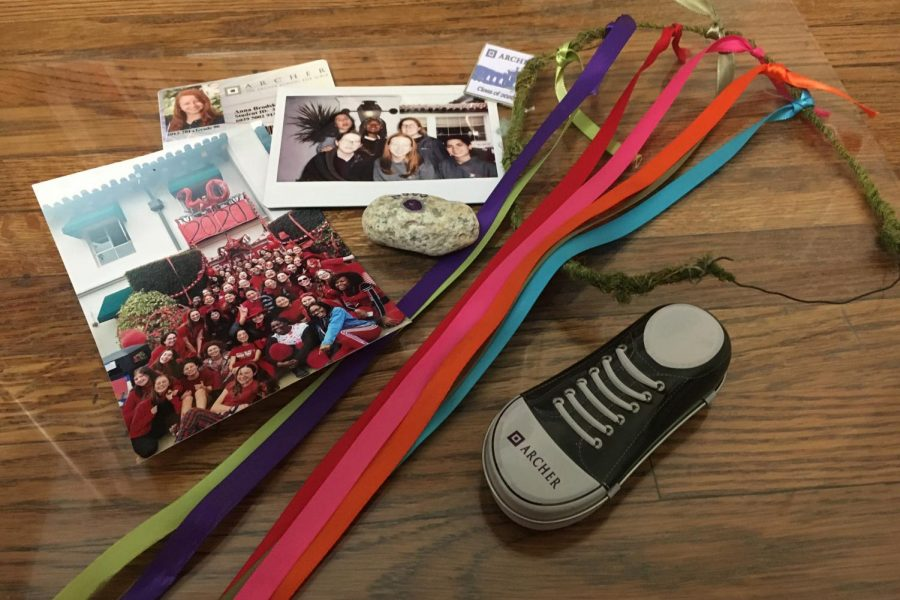 Mementos from my time at Archer, including the wreath I wore to weave the Maypole, a rock I painted on my first Fall Outing, my sixth grade OneCard and a photo of my friends on our last day of in-person classes.