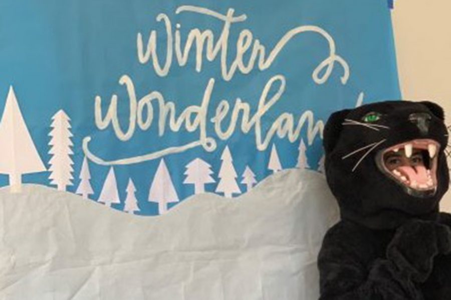 Archer's very own mascot, the Panther, poses in front of a Winter Wonderland poster from a previous celebration on campus. Due to the recent surge of COVID-19 cases, this year's Winter Wonderland caravan was cancelled until further notice.