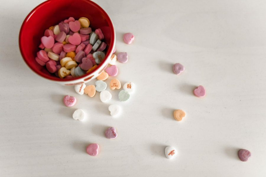 A cup of Valentine's Day candies are scattered across a table. On Feb. 13, the annual Galentine's Day celebration is held, which ceremonializes and commemorates the gift of friendship for all.