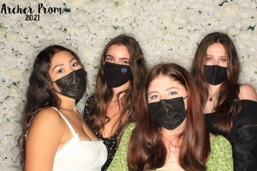 Seniors Mackenzie Turner, Lola Lamberg, Amelia Stone and Ava Salomon pose for a photo at the rose backdropped photo booth on May 1 during the evening senior prom celebration. The booth, set-up at Will Geer Theatricum Botanicum,