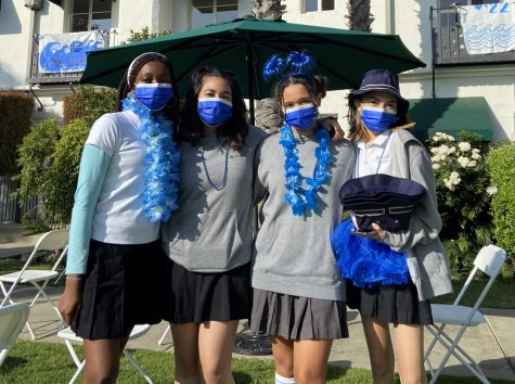 Rising seniors Chidimma Nwafor, Anny Rodriguez, Marley Mills and Andrea Ramirez pose for a photo together in the courtyard wearing their blue accessories. Ramirez holds blue bucket hats, which class reps bought for the entire rising senior class and senior mentors. On June 4, rising seniors spent Moving Up Day at school, commemorating their final hours as juniors.