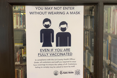A sign reminding community members to obey masking protocols is displayed on the door of the library. Other signs like this instructing students, faculty, staff and visitors to follow health and safety protocols in order to prevent the spread of COVID-19 are displayed around campus.