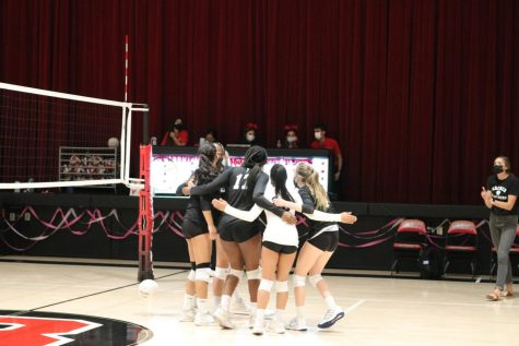 """The varsity volleyball team comes together in a huddle at their recent match against Buckley. """"Were all really great players individually, Milton said. [Were] just using our strengths as a team to keep persevering."""